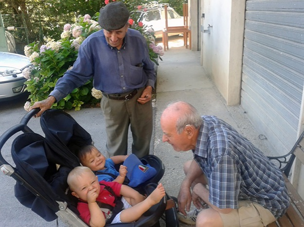 two older man play with two babies in a tandem stroller